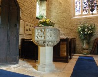 The 15th century font near the ancient door, looking west to some Easter lilies
