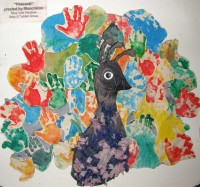 Most of the picture - the tail of the peacock - is made up of children's handprints